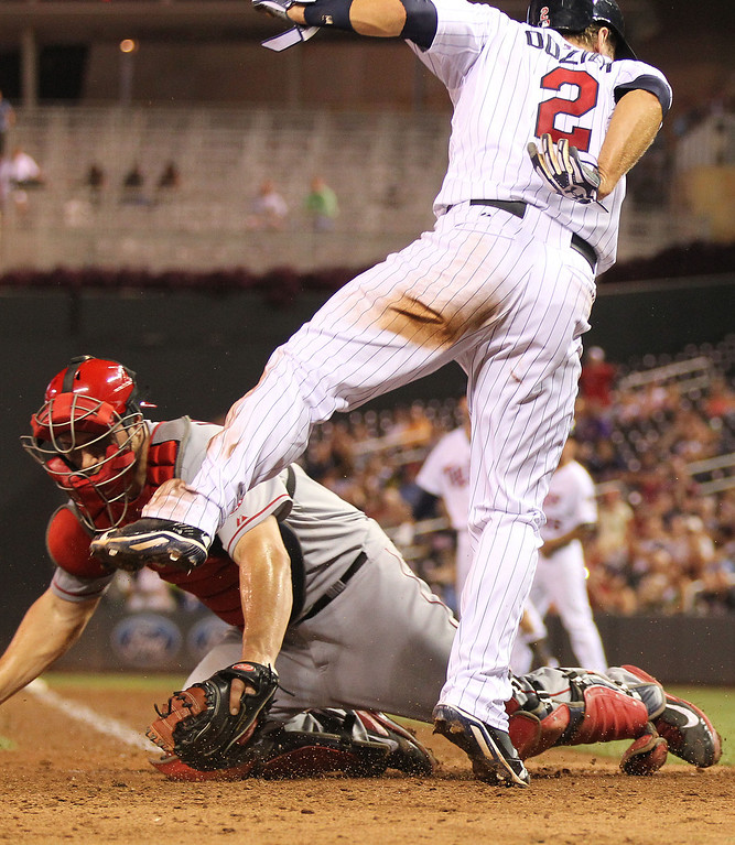 . Minnesota Twins Brian Dozier, left, slides safely into home base  after jumping over Los Angeles Angels catcher Chris Iannetta in the seventh inning of their baseball game in Minneapolis Monday, Sept. 9, 2013.(AP Photo/Andy Clayton-King)