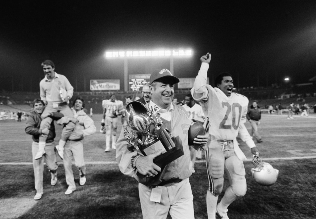 . Ohio State football coach Earle Bruce carries the victory trophy and game ball after his team defeated Brigham Young University 47-17 in the Holiday Bowl in San Diego, Calif., Dec. 18, 1982. (AP Photo/Lenny Ignelizi)