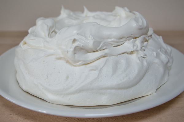 Pavlova base covered in whipped cream