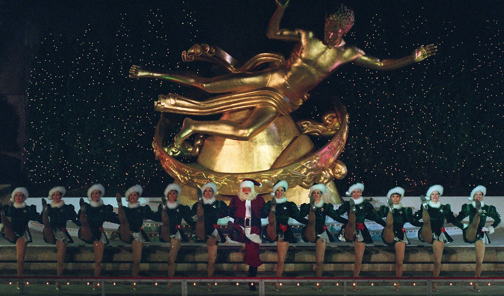 . Santa does a high kick flanked by the Radio City Rockettes as they perform in the ice skating rink at New York\'s Rockefeller Plaza shortly before the 26,000 lights decorating the Rockefeller Center Christmas tree were switched on Tuesday night, Dec. 2, 1997.  The 74-foot Norway spruce came from Stony Point, N.Y.  (AP Photo/Ed Bailey)