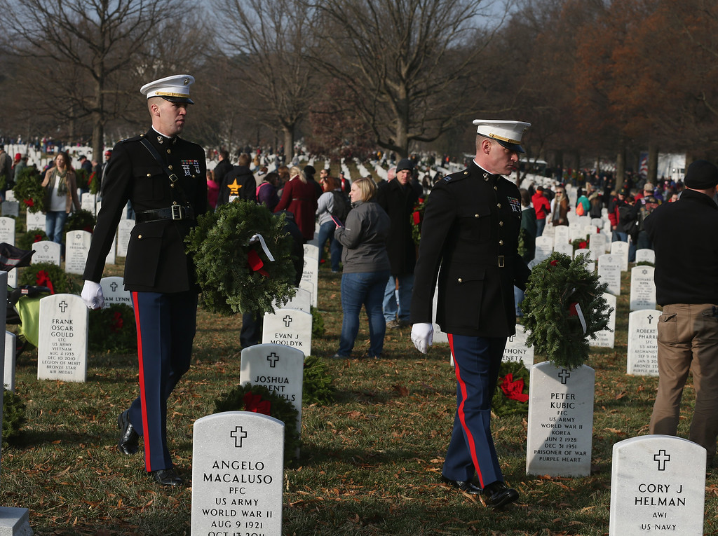 . U.S. Marines Capt. Benjamin O\'Donnell (R) and Capt. Mike Harvey (L) look for a Marine graves to place wreaths on during the National Wreaths Across America Day at Arlington National Cemetery, December 13, 2014 in Arlington, Virginia. Volunteers placed wreaths throughout the entire cemetery in honor of Arlingtons 150th anniversary.  (Photo by Mark Wilson/Getty Images)