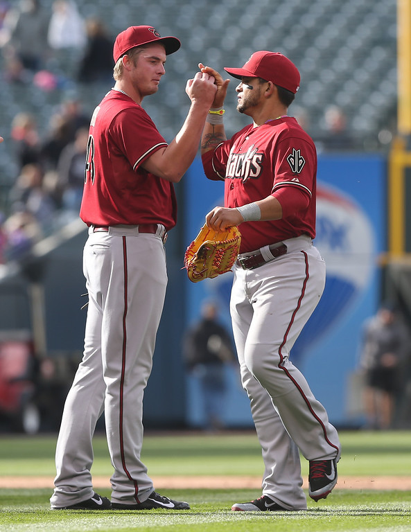 . Arizona Diamondbacks relief pitcher Adison Reed, left, is congratulated by right fielder Gerardo Parra after Reed retired the Colorado Rockies to earn his second save of the season in the ninth inning of the Diamondbacks\' 5-3 victory in the MLB National League baseball game in Denver on Sunday, April 6, 2014. (AP Photo/David Zalubowski)