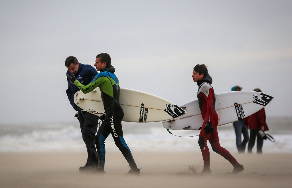 . A police officer asks two young surfers to leave the beach at the North Sea in Blankenberge, Belgium, 05 December 2013. Storm \'Xaver\' will hit the Belgian North Sea with heavy gusts and a wind velocity of more than 100 kilometers per hour on 05 December.  EPA/JULIEN WARNAND