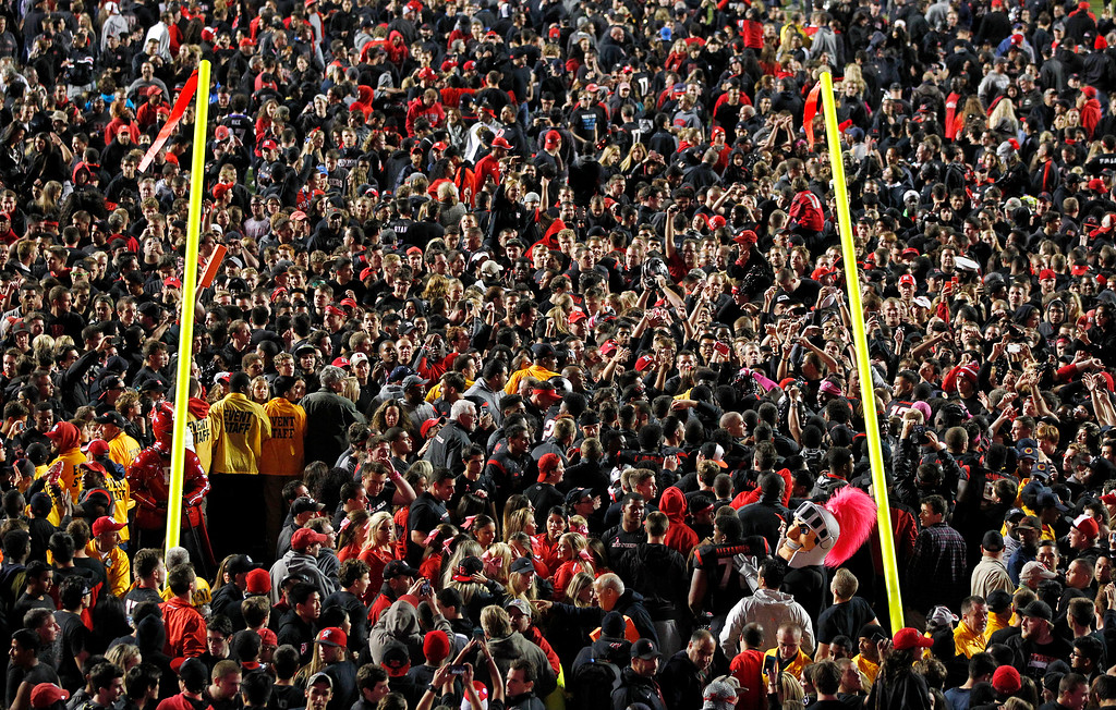 . The Rutgers mascot is seen in the lower right as fans flood the field after Rutgers defeated Michigan 26-24 in an NCAA college football game Saturday, Oct. 4, 2014, in Piscataway, N.J. (AP Photo/Rich Schultz)