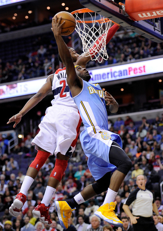 . Denver Nuggets point guard Ty Lawson, right, goes to the basket against Washington Wizards guard John Wall (2) during the first half of an NBA basketball game, Friday, Feb. 22, 2013, in Washington. (AP Photo/Nick Wass)