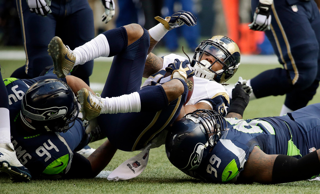 . St. Louis Rams running back Tre Mason, center, is tackled by Seattle Seahawks defensive tackles Tony McDaniel (99) and Kevin Williams (94) in the first half of an NFL football game, Sunday, Dec. 28, 2014, in Seattle. (AP Photo/Elaine Thompson)