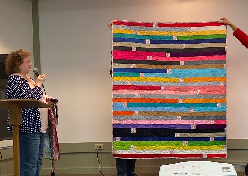 Janet Keesler showed us her Jelly Roll Race quilt.  Janet inserted a flower pattern at the end of each strip.