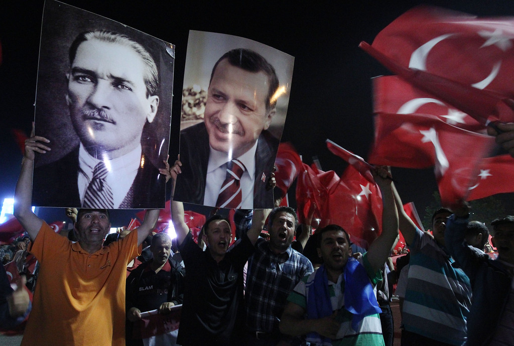 . Supporters of the AKP, Justice and Development party hold the portraits of Mustafa Kemal Ataturk, founder of Turkey and Turkish Prime Minister Recep Tayyip Erdogan at the Ataturk Airport of Istanbul early Friday, June 7, 2013. Erdogan took a combative stance on his closely watched return to the country early Friday, telling supporters who thronged to greet him that the protests that have swept the country must come to an end. In the first extensive public show of support since anti-government protests erupted last week, more than 10,000 supporters cheered Erdogan with rapturous applause outside Istanbul\'s international airport. (AP Photo/Thanassis Stavrakis)