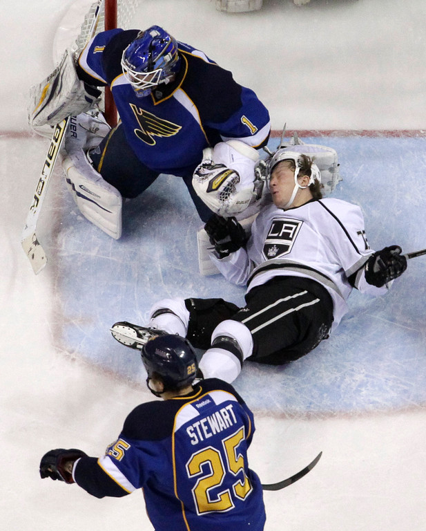 . Los Angeles Kings\' Tyler Toffoli, right, falls as St. Louis Blues goalie Brian Elliott, top, and Blues\' Chris Stewart (25) defend during the first period in Game 5 of a first-round NHL hockey Stanley Cup playoff series, Wednesday, May 8, 2013, in St. Louis. (AP Photo/Jeff Roberson)