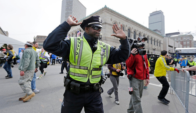 . A Boston police officer clears Boylston Street following an explosion at the finish line of the 2013 Boston Marathon in Boston, Monday, April 15, 2013. Two explosions shattered the euphoria at the finish line on Monday, sending authorities out on the course to carry off the injured while the stragglers were rerouted away from the smoking site of the blasts. (AP Photo/Charles Krupa)