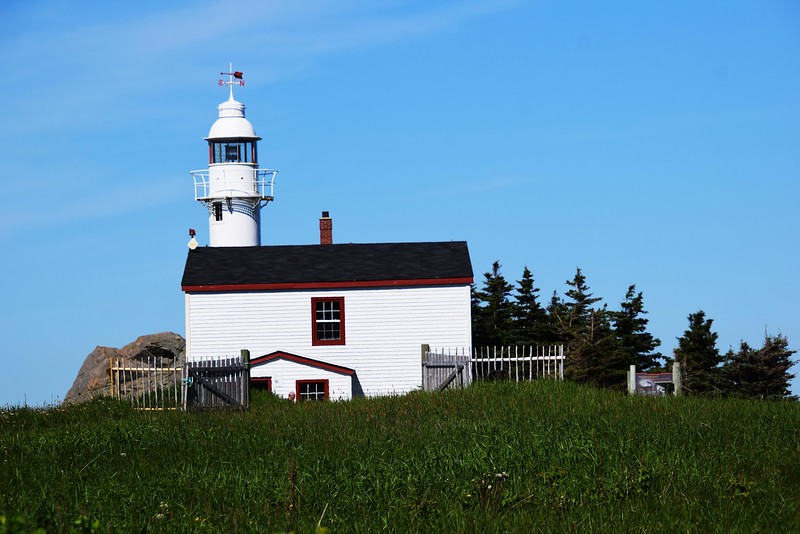 white lighthouse on small hill