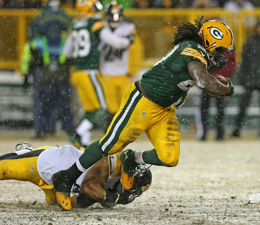 . Eddie Lacy #27 of the Green Bay Packers is tripped up by Chris Carter #54 of the Pittsburgh Steelers at Lambeau Field on December 22, 2013 in Green Bay, Wisconsin.  (Photo by Jonathan Daniel/Getty Images)