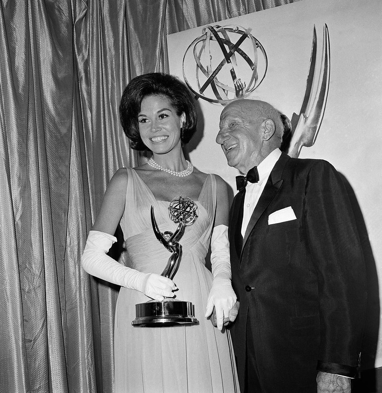 . Mary Tyler Moore, who plays Dick Van Dyke\'s wife on his television show, holds the Television Academy Emmy for outstanding individual achievement awarded to him, in Hollywood, Calif., Sept. 12, 1965. With her is Jimmy Durante who made the presentation. Van Dyke, a previous Emmy winner, was not present at the awards show. (AP Photo/Richard Strobel)