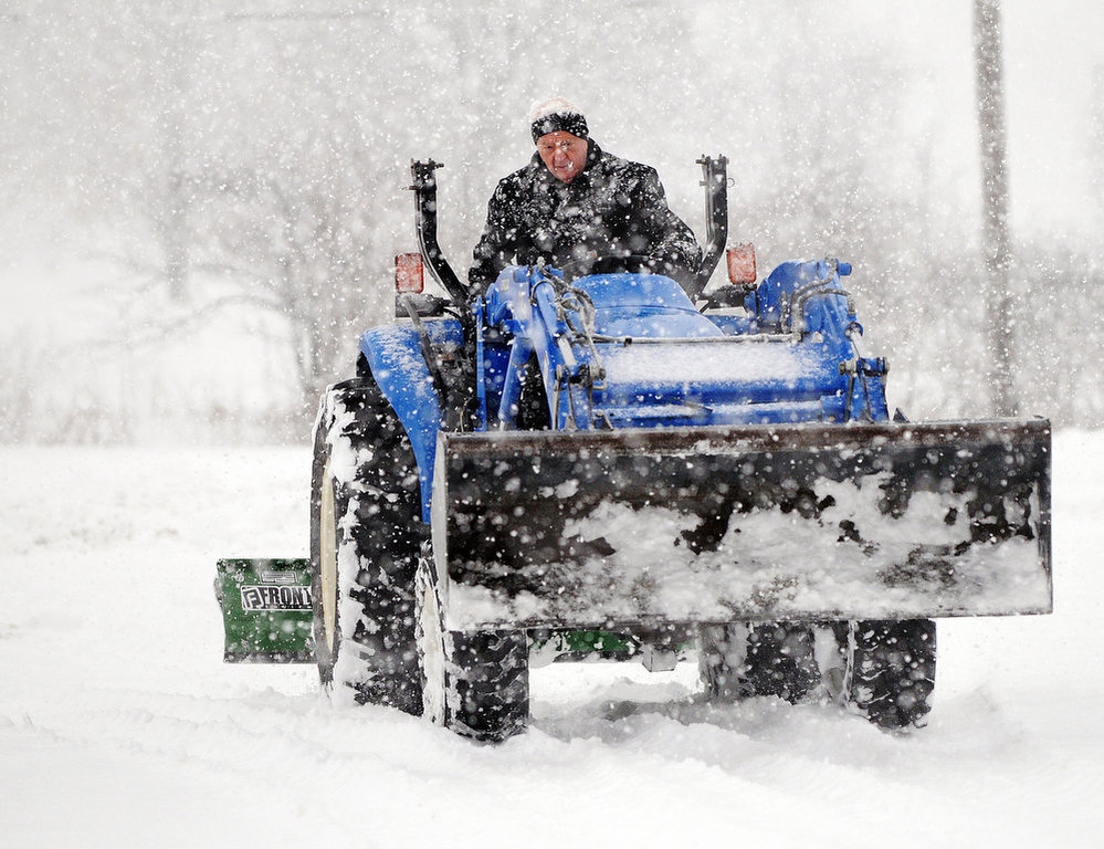 . Kent Farley clears a parking lot of snow on Tuesday, March 5, 2013, in Coal Valley, Ill. (AP Photo/The Dispatch, Todd Mizener)