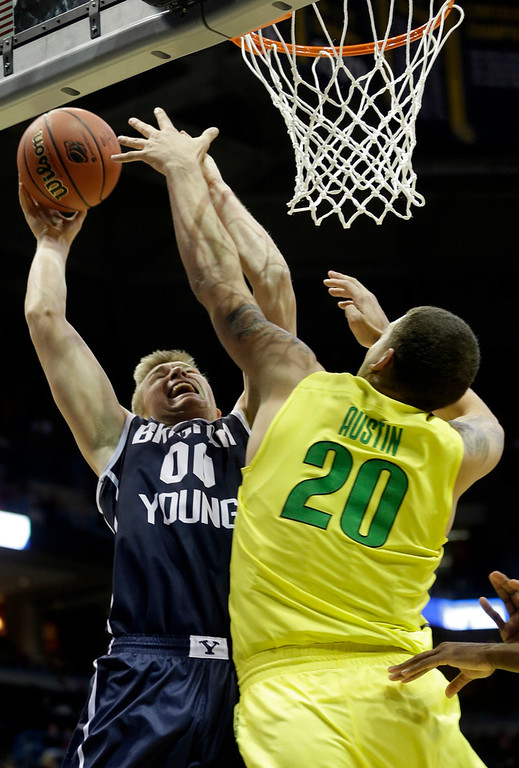 . BYU forward Eric Mika (00) is fouled by Oregon center Waverly Austin (20) as he takes a shot during the first half of a second-round game in the NCAA college basketball tournament Thursday, March 20, 2014, in Milwaukee. (AP Photo/Morry Gash)