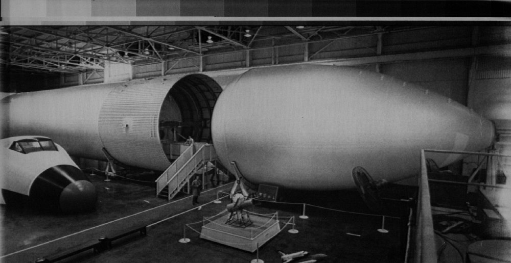 Description of . This early production model of the shuttle's external tank is on display at the Marshall Space Flight Center. The tank which holds 224,000 pounds of liquid hydrogen in the rear portion, 1,332,000 pounds of liquid oxygen in the container at right. Two people visible in the center of the two sections are dwarfed by the tanks 154.2 feet length and 27.5 feet diameter. When fully loaded the tank is the largest and heaviest element of the Shuttle weight is 1,638,565 pounds.  Denver Post Library Archive