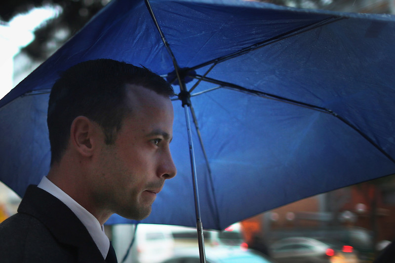 . Oscar Pistorius shelters from the rain as he makes his way to North Gauteng High Court for the second day of his trial accused of the murder of his girlfriend Reeva Steenkamp on March 4, 2014 in Pretoria, South Africa. Olympic and Paralympic athlete Oscar Pistorius, aged 27, is accused of murdering his girlfriend Reeva Steenkamp. Pistorius denies the allegation claiming he mistook Steenkamp for an intruder inside their home on Valentines Day 2013.  (Photo by Christopher Furlong/Getty Images)