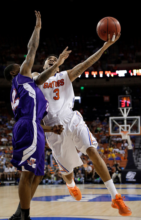 . Florida\'s Mike Rosario (3) goes up for a shot as Northwestern State\'s Jalan West (12) defends during the first half of a second-round game of the NCAA men\'s college basketball tournament Friday, March 22, 2013, in Austin, Texas. (AP Photo/David J. Phillip)