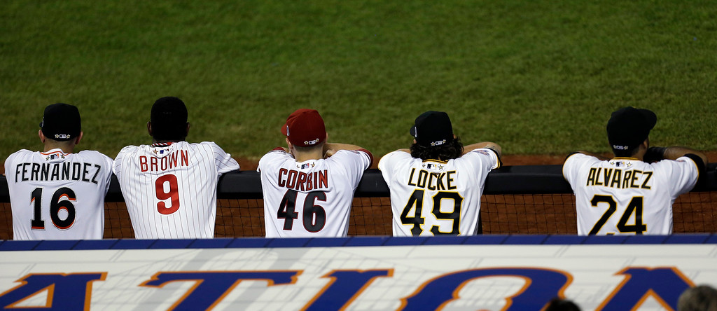 . National League players watch from the dugout during the sixth inning of the MLB All-Star baseball game, on Tuesday, July 16, 2013, in New York. (AP Photo/Julio Cortez)