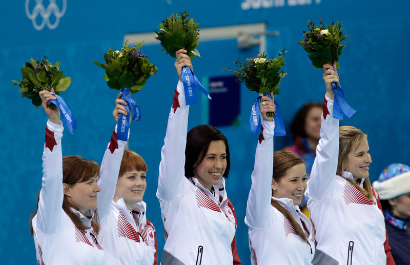 . Canada\'s gold medal winning curling team, from left, Kirsten Wall, Dawn McEwen, Jill Officer, Kaitlyn Lawes, and skip Jennifer Jones raise their arms their arms during the flower ceremony after defeating Sweden in women\'s curlingat the 2014 Winter Olympics, Thursday, Feb. 20, 2014, in Sochi, Russia. (AP Photo/Robert F. Bukaty)