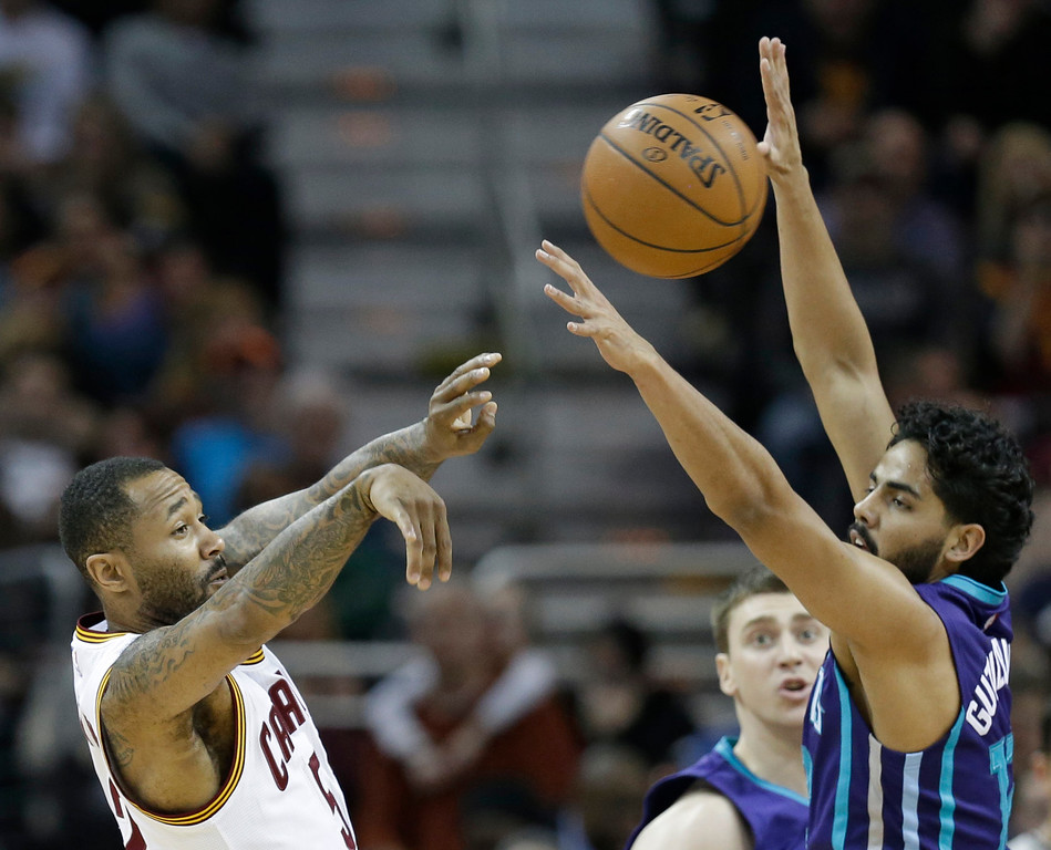 . Cleveland Cavaliers\' Mo Williams, left, passes over Charlotte Hornets� Jorge Gutierrez, from Mexico, in the second half of an NBA basketball game Wednesday, Feb. 24, 2016, in Cleveland. The Cavaliers won 114-103. (AP Photo/Tony Dejak)
