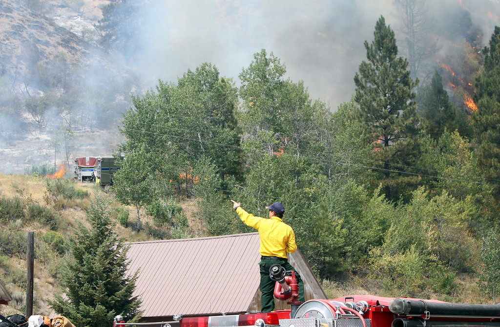 . Firefighters watch as the Elk Complex fire burns in Pine, Idaho, on Monday, Aug. 12, 2013. (AP Photo/The Idaho Statesman, Joe Jaszewski)