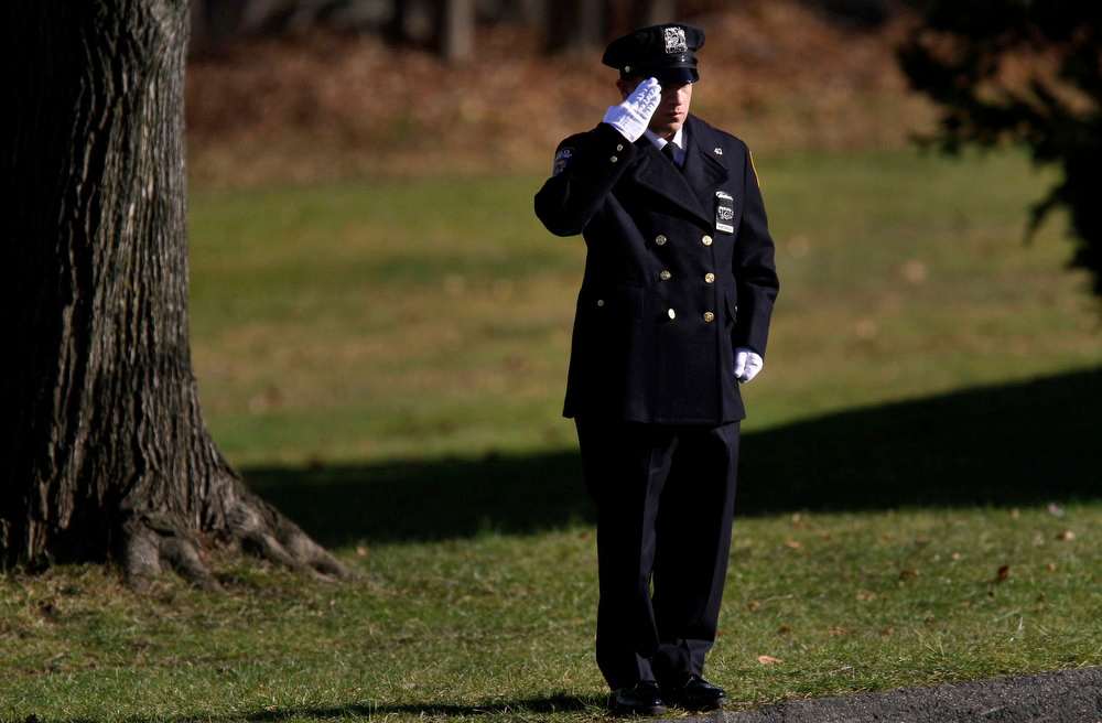 . A police officer salutes the family of six-year-old Sandy Hook Elementary School shooting victim Catherine Hubbard during her funeral at Saint Rose of Lima Roman Catholic Church in Newtown, Connecticut December 20, 2012. Even as they buried more victims of the second-deadliest school shooting in U.S. history on Thursday, residents of Newtown, Connecticut, looked for ways to pressure national leaders to restrict access to weapons.  REUTERS/Joshua Lott