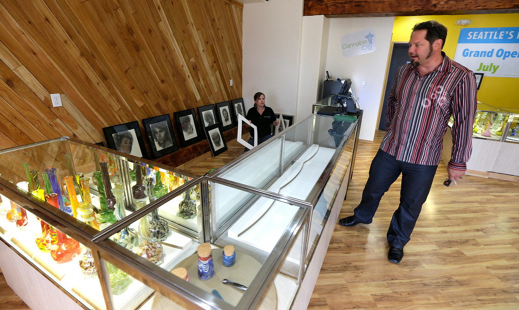 . James Lathrop, right, the owner of the recreational marijuana store Cannabis City, checks out display case with glass bongs on display and an empty area awaiting actual marijuana, Monday, July 7, 2014, in Seattle.  (AP Photo/Ted S. Warren)