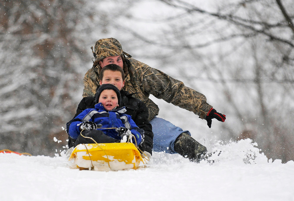. Tracey Ferguson falls to the ground behind his sons Colten Ferguson, 5, and Collin Ferguson, 9, after giving them a push down the hill at Riverside Park in Murphysboro, Ill. Wednesday, Dec. 26, 2012. (AP Photo/The Southern Illinoisan, Aaron Eisenhauer)