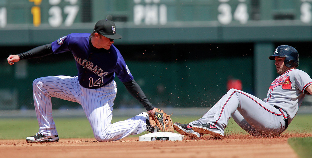 . Colorado Rockies second baseman Josh Rutledge (14) cannot make the tag as Atlanta Braves\' Dan Uggla (26) slides safely into second with a double during the second inning of a baseball game, Wednesday, April 24, 2013, in Denver. The Rockies won 6-5 in the 12th inning. (AP Photo/Barry Gutierrez)