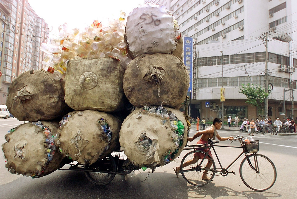 . An enterprising Chinese man pulls a bicycle cart packed high with bags of recyclable plastic containers in Shanghai July 25, 2002. The man sells each kilogram (2.2 pounds) of plastic for 0.08 yuan ($.01) to a nearby depot. REUTERS/Claro Cortes IV