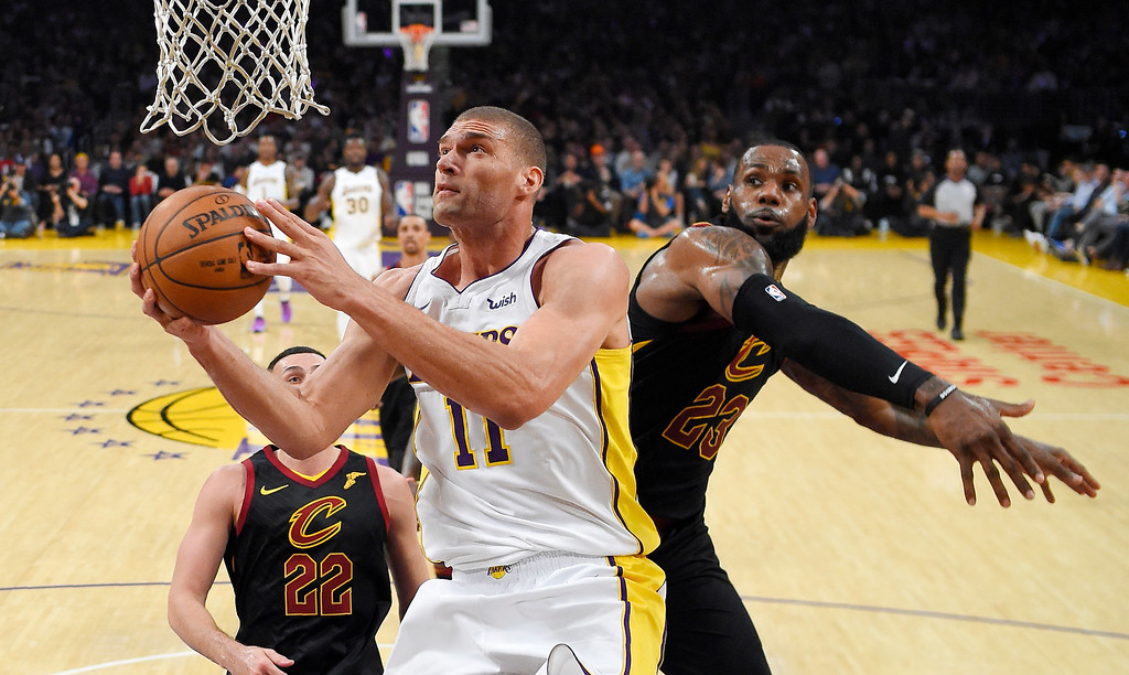 . Los Angeles Lakers center Brook Lopez, left, shoots as Cleveland Cavaliers forward LeBron James takes a swipe at it during the first half of an NBA basketball game, Sunday, March 11, 2018, in Los Angeles. (AP Photo/Mark J. Terrill)