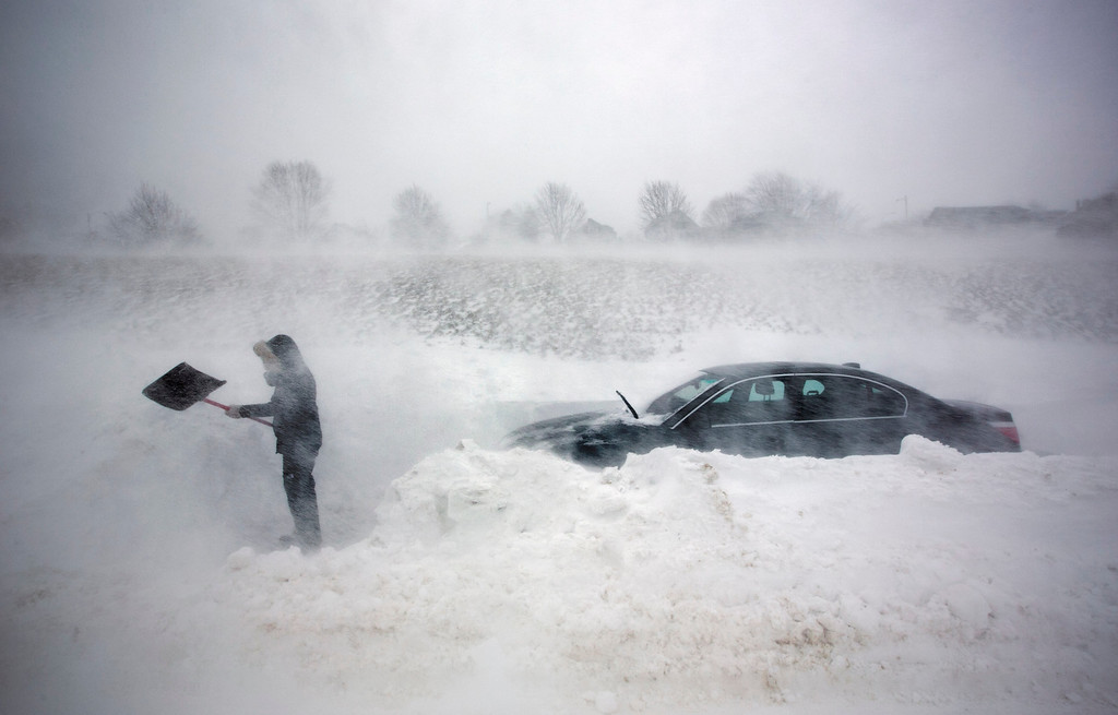 . A woman digs out her car after it was blocked in by drifting snow during a blizzard, Saturday, Feb. 9, 2013, in Portland, Maine. The storm dumped more than 30 inches of snow as of Saturday afternoon, breaking the record for the biggest storm on record. (AP Photo/Robert F. Bukaty)
