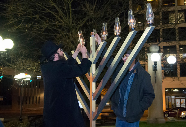 12/26/19 Wesley Bunnell | StaffrrRabbi Yosef Rivkin, L, assists as a Menorah is lit on Thursday December 26, 2019 in Central Park.