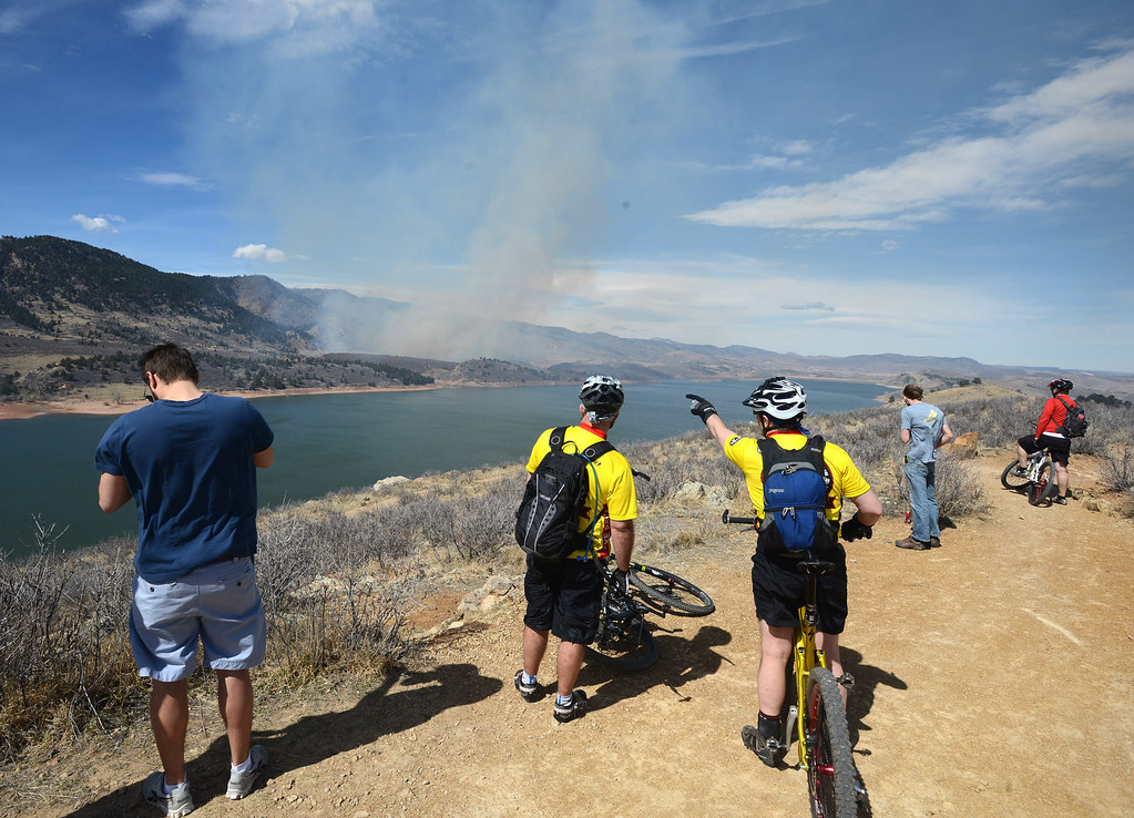 . Onlookers stop to watch the fire on the east side of Horsetooth Reservior west of Fort Collins, Colo., on Friday, March 15, 2013. The 40-acre wildfire burning in gusty winds and warm weather was threatening homes west of Fort Collins on Friday and prompted about 50 people to leave the area. (AP Photo/The Coloradoan, V. Richard Haro)
