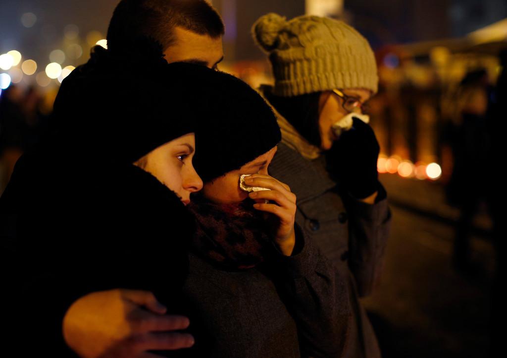 . Passers by react outside the collapsed Maxima supermarket in Riga, Latvia, Thursday, Nov. 21, 2013.  (AP Photo/Mindaugas Kulbis)