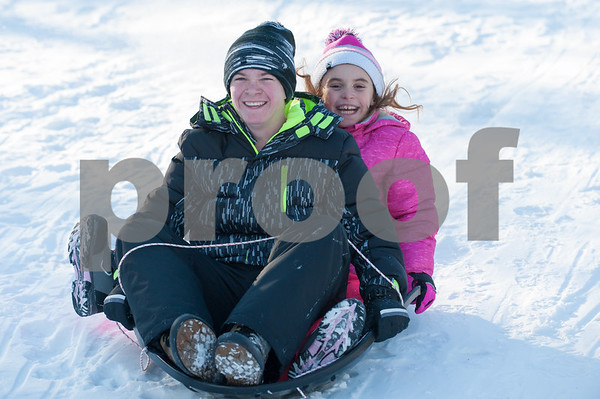 12/26/17 Wesley Bunnell | Staff Families took advantage of good sledding conditions at Page Park on Tuesday afternoon. Jedric Setula, age 12, and sister Corinne Setula, age 9, slide down the hill towards the tennis courts.