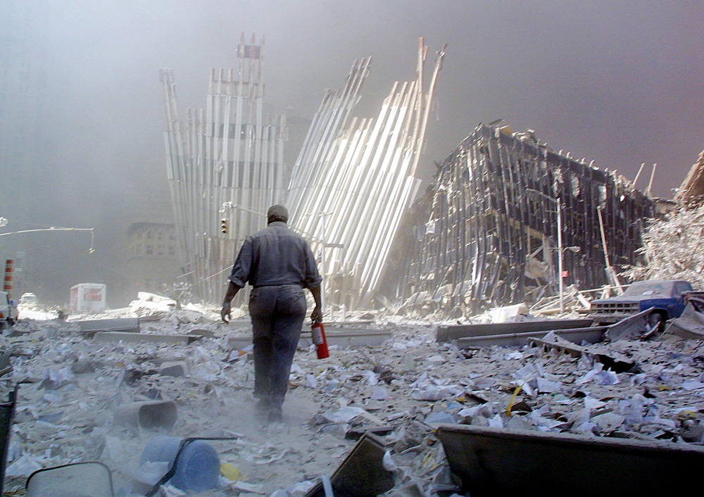 . A man with a fire extinguisher walks through rubble after the collapse of the first World Trade Center Tower 11 September, 2001, in New York. The man was shouting as he walked looking for victims who needed assistance. Both towers collapsed after being hit by hijacked passengers planes.    AFP PHOTO  Doug KANTER