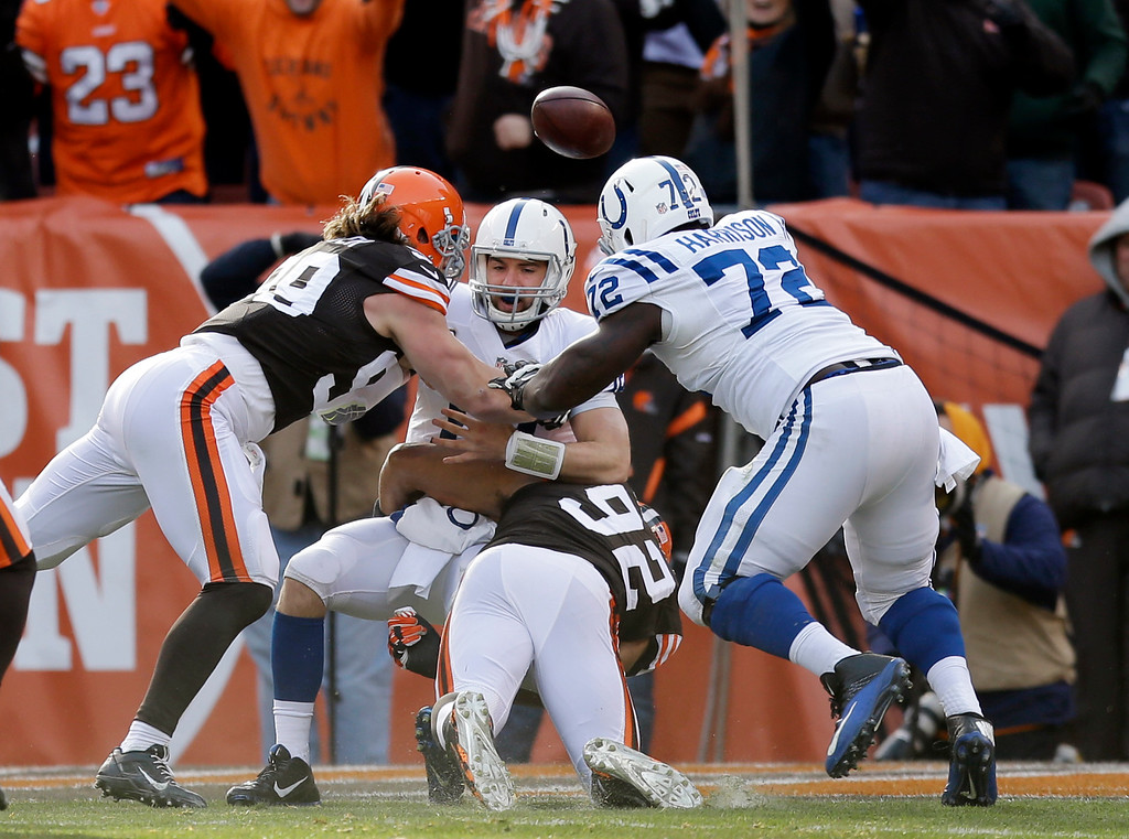 . Indianapolis Colts quarterback Andrew Luck, center, fumbles the ball against Cleveland Browns outside linebacker Paul Kruger (99) in the first quarter of an NFL football game Sunday, Dec. 7, 2014, in Cleveland. The Browns recovered in the end zone for a touchdown. (AP Photo/Tony Dejak)
