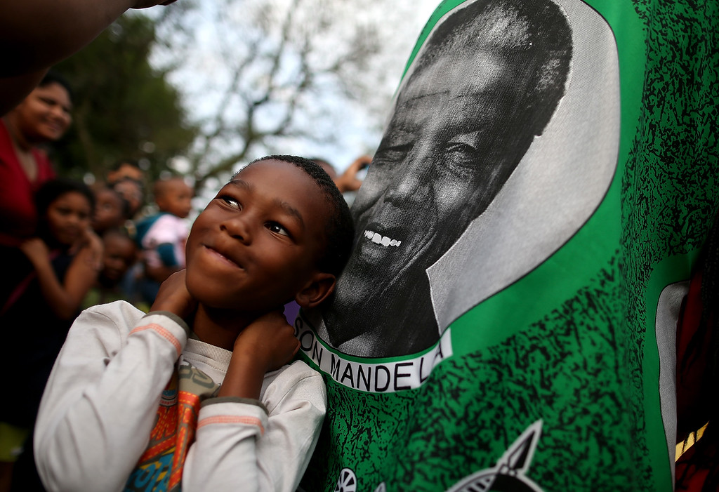 . A young boy stands next to an image of Nelson Mandela outside of Mandela\'s home on December 7, 2013 in Johannesburg, South Africa. Mandela, also known as Tata Madiba, passed away on the evening of December 5th at his home in Houghton at the age of 95. Mandela became South Africa\'s first black president after being jailed for decades for his activism against apartheid in a racially-divided South Africa. (Photo by Justin Sullivan/Getty Images)