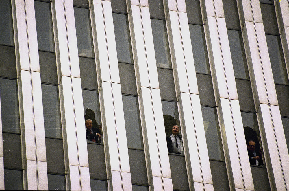 Description of . Workers peer through broken windows of the World Trade Center in New York on Feb. 26, 1993, after an explosion in an underground garage rocked the twin towers complex.  Heavy smoke, caused by underground fires, was reported throughout the buildings, causing the evacuation of the buildings.  (AP Photo/Alex Brandon)