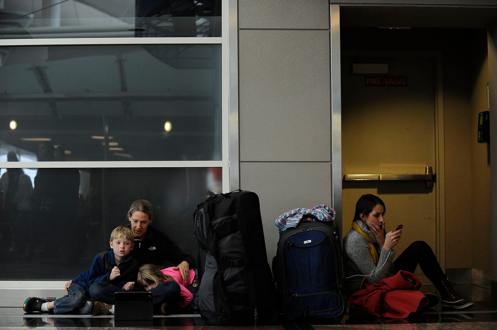 . Diana Childers, Luke Childers, 7, Kiley Childers, 4, from San Diego and Rebecca Garcia from New York, right, rest in the West Terminal at Denver International Airport on Sunday, February, 24, 2013 as they wait after their flights were cancelled earlier in the day. A major winter storm caused the cancellation of nearly 200 flights at DIA on Sunday. Seth A. McConnell, The Denver Post