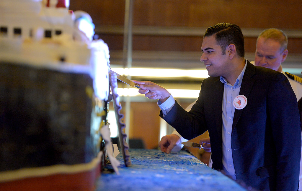 . After the ceremonial cutting of the birthday cake, Long Beach Mayor Robert Garcia goes in for a small piece of his own as the Queen Mary celebrated its 80th anniversary of her launching by inviting the public to tour the ship for free in Long Beach, CA on Friday, September 26, 2014. After some speeches and a short film, guests were able to sample a slice of cake from a 15-foot long, 600-pound replica of the ship made by baker Jose Barajas. (Photo by Scott Varley, Daily Breeze)