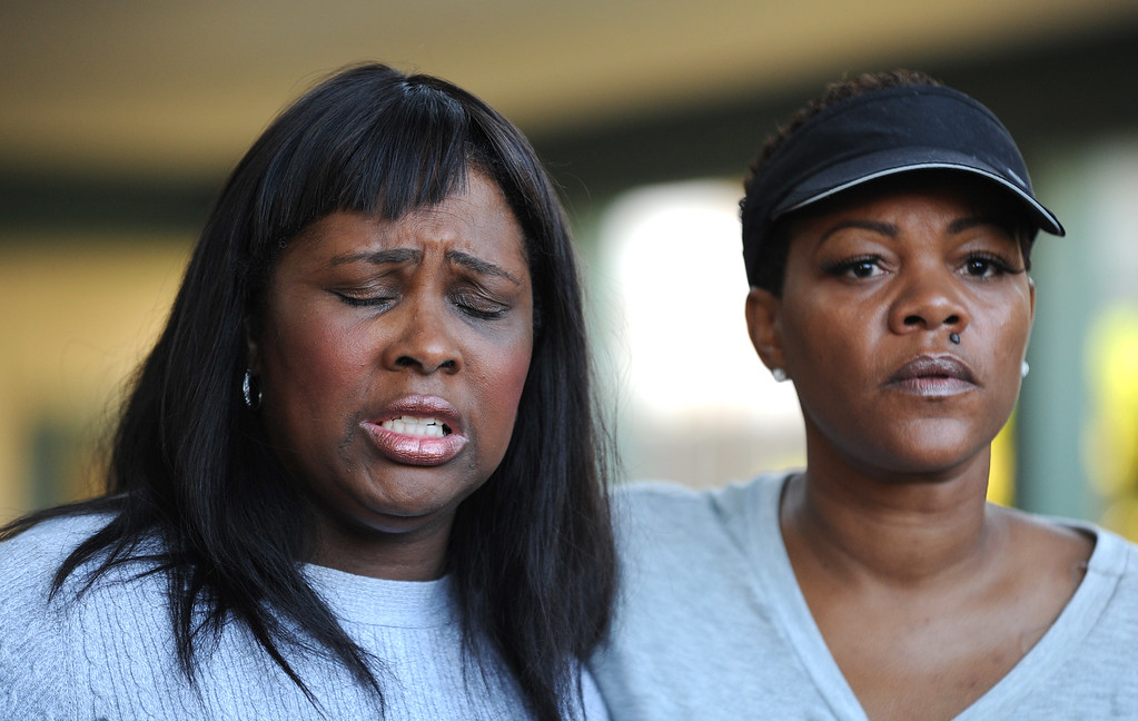 . Stacy Hogg, right, and Wanda Johnson, the mother of the late Oscar Grant, plead for peace on the streets of Oakland during a prayer vigil on the 3400 block of Wilson Ave. in Oakland, Calif., on Thursday, July 18, 2013. One young girl was killed and 3 other people were wounded when an unknown gunman fired shots through the door of the apartment on Wilson Avenue. (Dan Honda/Bay Area News Group)