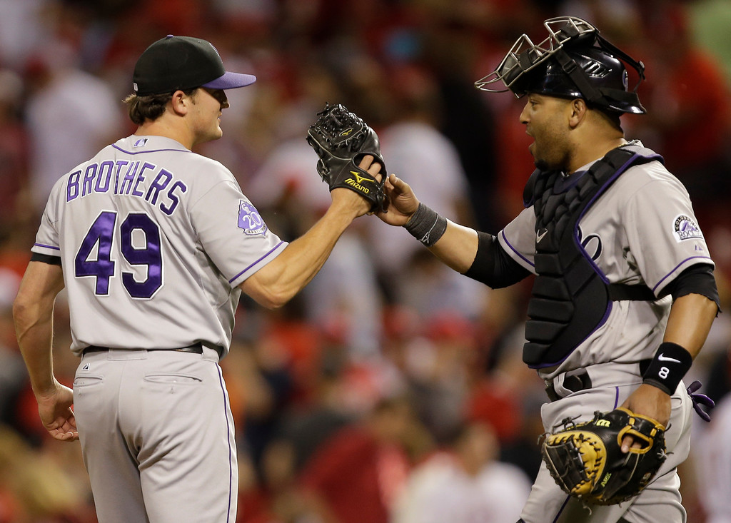 . Colorado Rockies relief pitcher Rex Brothers (49) is congratulated by catcher Yorvit Torrealba after they defeated the Cincinnati Reds 5-4 in a baseball game, Tuesday, June 4, 2013, in Cincinnati. Brothers earned his second save. (AP Photo/Al Behrman)