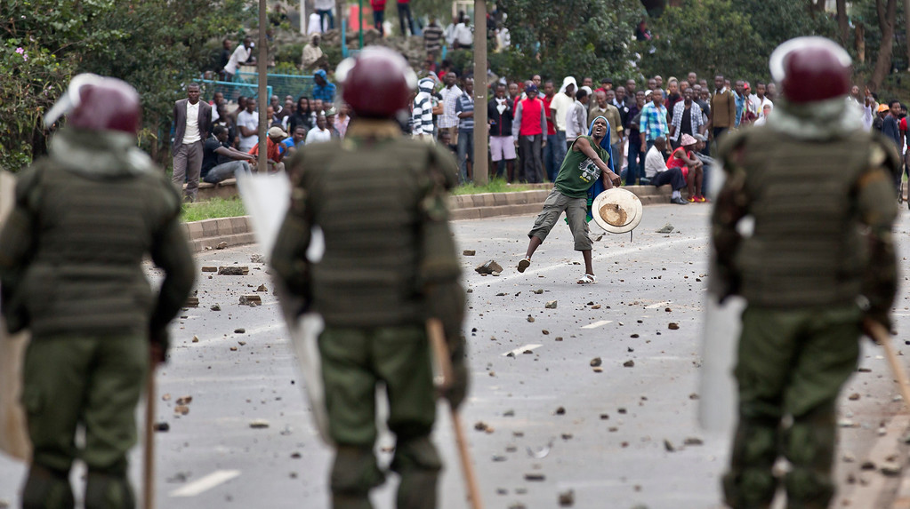 . A student carrying a makeshift shield throws rocks at riot police as they engage in running battles on the highway next to Nairobi University\'s main campus in downtown Nairobi, Kenya Tuesday, May 20, 2014. Kenyan university students on Tuesday carried out demonstrations over a proposed increase in student fees, but the protests quickly turned into hours of running battles between students throwing rocks and security forces firing tear gas, before riot police chased the students inside their campus and cornered them in a building into which they fired dozens of tear gas grenades and for a while prevented anyone from leaving. (AP Photo/Ben Curtis)