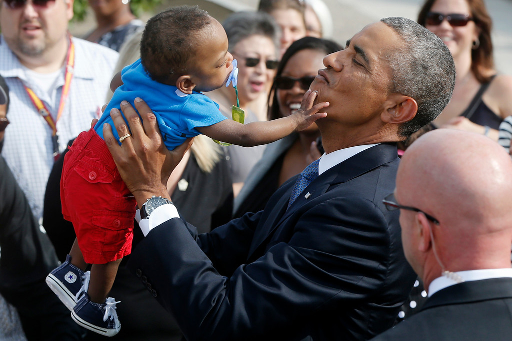 . President Barack Obama picks up 13-month-old Larnell Maurice Perry Jr., grandson of Angelene C. Carter, who was killed in the September 11 attacks at the Pentagon, at the Pentagon, Thursday, Sept. 11, 2014, during a ceremony where Obama marked the 13th anniversary of the 9/11 attacks.  (AP Photo/Charles Dharapak)