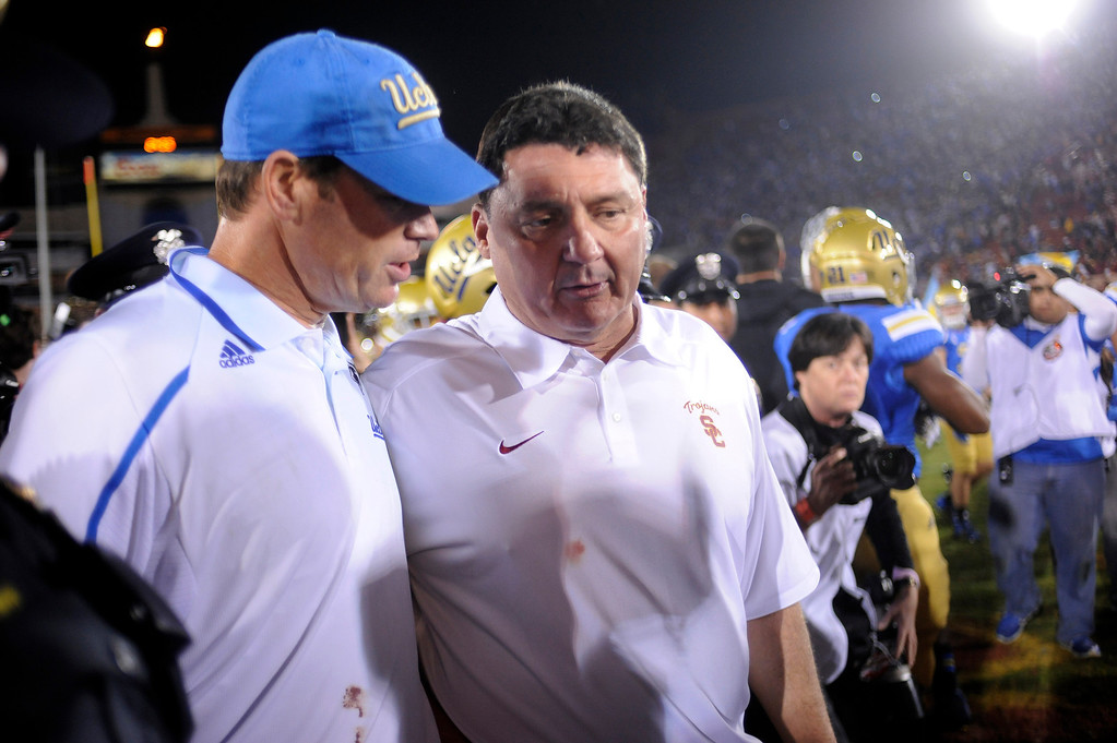 . USC interim head coach Ed Orgeron and UCLA head coach Jim Mora after their game at the Los Angeles Memorial Coliseum Saturday, November 30, 2013.  UCLA beat USC 35-14. (Photo by Hans Gutknecht/Los Angeles Daily News)