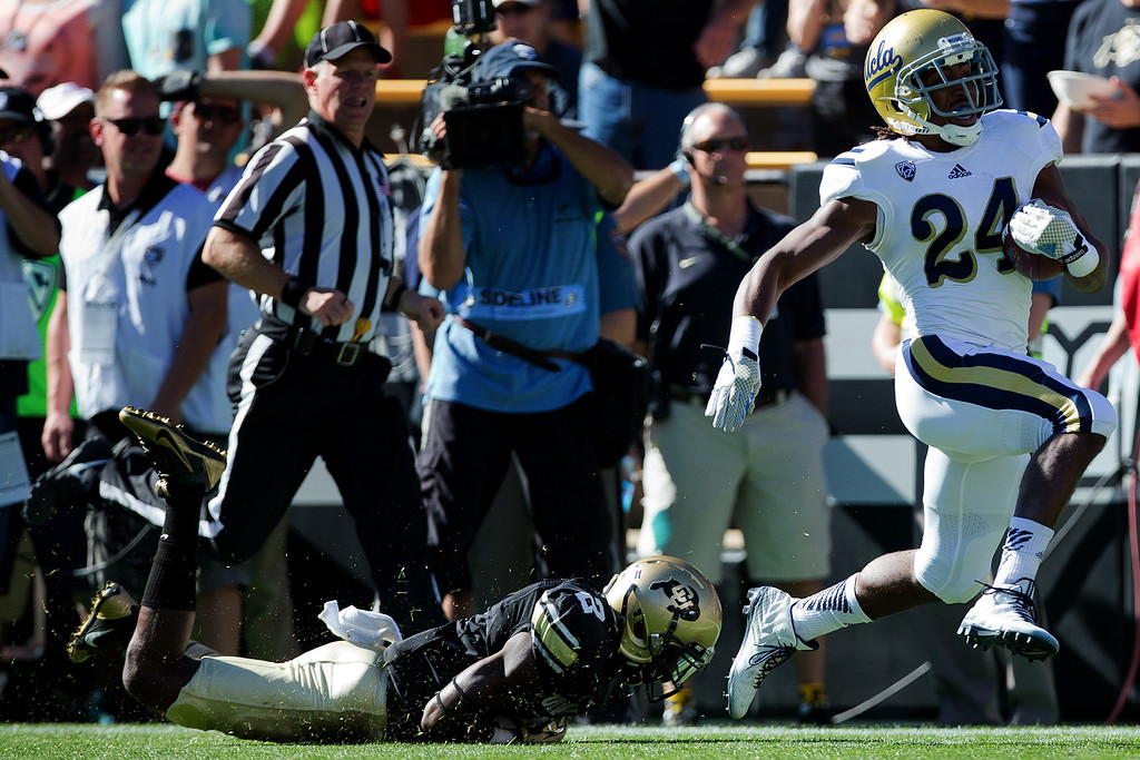 . BOULDER, CO - OCTOBER 25:  Running back Paul Perkins #24 of the UCLA Bruins runs past cornerback Kenneth Crawley #2 of the Colorado Buffaloes for a 93-yard touchdown during the first quarter at Folsom Field on October 25, 2014 in Boulder, Colorado. (Photo by Justin Edmonds/Getty Images)