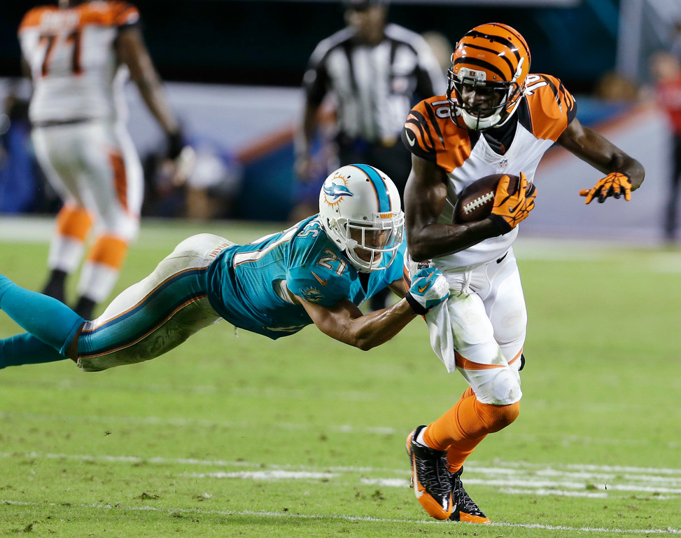 . Miami Dolphins cornerback Brent Grimes (21) tackles Cincinnati Bengals wide receiver A.J. Green (18) during the second half of an NFL football game, Thursday, Oct. 31, 2013, in Miami Gardens, Fla. (AP Photo/Lynne Sladky)